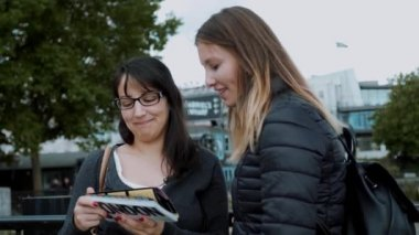 Two girls read a travel guide in the city center of London