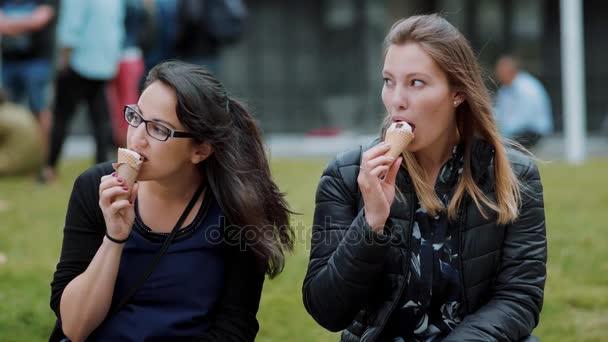 Dvě dívky sedí na loukách v parku a jíst zmrzlinu
