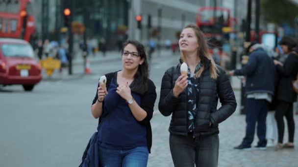 Dvě mladé ženy projít z londýnské city s ice cream - Londýn - Anglie - 5. září 2017