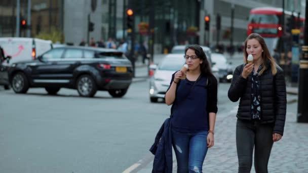 Dvě mladé ženy projít z londýnské city se zmrzlinou v pomalém pohybu - Londýn - Anglie - 5. září 2017