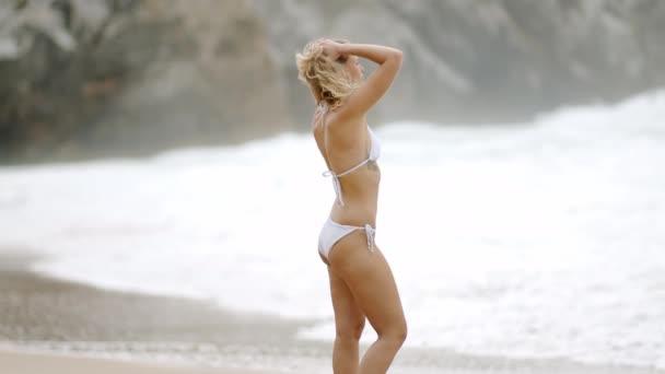 Vonzó lány, aki a homokos parton pihen. Napközbeni felvételek