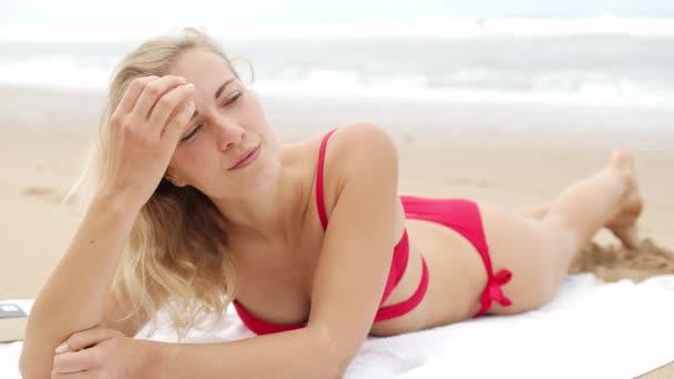 sexy Frau im Bikini entspannt am Sandstrand am Meer