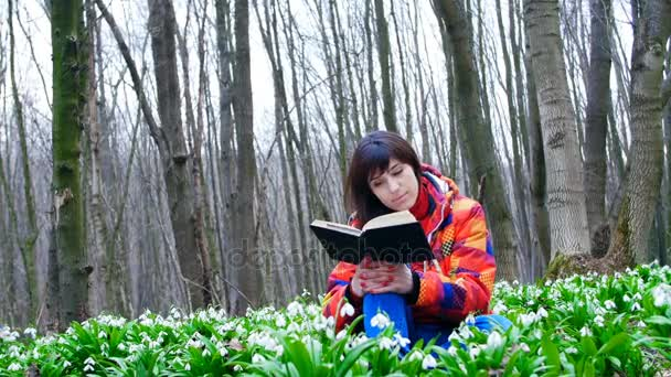 A beautiful smart girl is reading an interesting book in a spring forest full of blossoming snowdrops