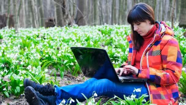 Egy gyönyörű fiatal lány dolgozik a laptop közepén a tavaszi erdő tele van virágzó hóvirág