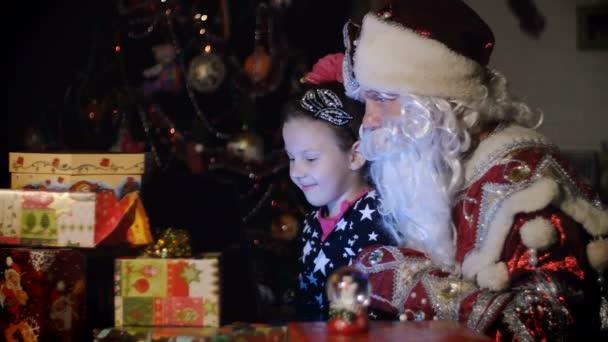 V šeru noci, mezi dary v zářivě barevných papírových krabičkách, hezká blondýnka holka s růžovou mašlí ve vlasech a v krásné šaty a Santa Claus, Ježíšek, otec