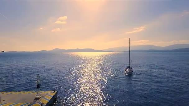 Západ slunce prázdné řecké Marina, Methana, Středozemní moře. Aero video fotografování, osamělá plachetnice vstupuje do přístavu. V pozadí, krajina od moře, jasné modré nebe, slunné