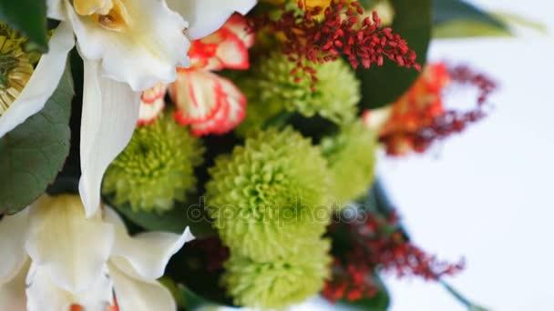 detail, rotace na bílém pozadí, květinová kompozice se skládá z Rose penny lane, karafiátů, orchideje Cymbidium, Zlatobýl, chryzantéma santini, Russus, aspidistra