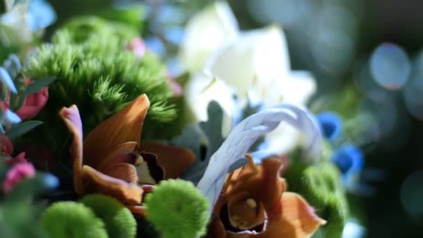 close-up,Flower bouquet in the rays of light, rotation, consists of Amaryllis white, Rose lydia, Santini , cineraria, eucalyptus, Ivy roomy, Barbatus, feverweed, Cymbidium orchid,