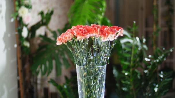 Kytice v paprscích světla, rotace, květinové kompozice tvoří zářivě oranžové turecké karafiátu. V pozadí hodně zeleně