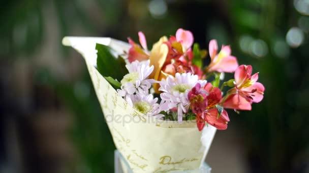 Kytice v paprscích světla, rotace, květinová kompozice se skládá z orchidejí Cymbidium, kosatců, chryzantéma. V pozadí hodně zeleně