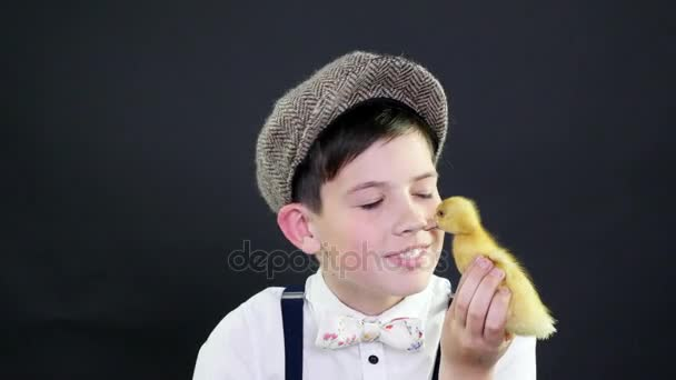 319ffbc17ad Πορτραίτο, ένα όμορφο αγόρι με ένα καπάκι και τιράντες που παίζει με ένα  μικρό κίτρινο παπάκι. Στούντιο ...