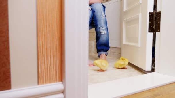 WC, in der Toilette, ist das Mädchen auf der Toilette sitzend, können Sie ihre Beine in Jeans sehen, sie ist barfuss. Neben ihr auf dem Boden drei schöne kleine gelbe Entlein Spaziergang