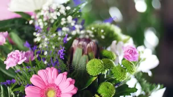 Nahaufnahme, Blumenstrauß in den Lichtstrahlen, Rotation, die florale Komposition besteht aus Chrysanthemen-Anastase, Zigeunerblume, Solidago, Barbatus, Protea, Nelke, Gerbera,