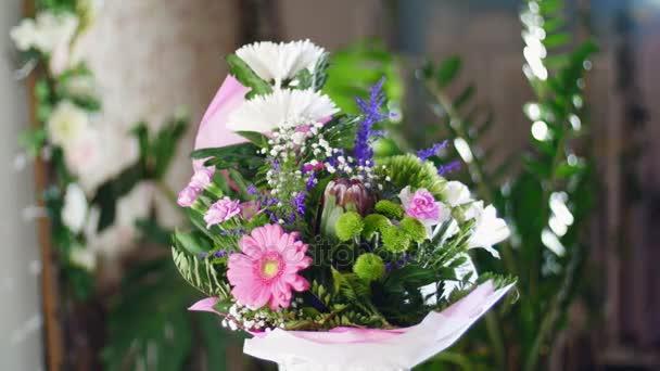 Kytice v paprscích světla, rotace, květinová kompozice se skládá z Chrysanthemum anastasis, gypsophila, Zlatobýl, Barbatus, Protea, karafiát, gerbera