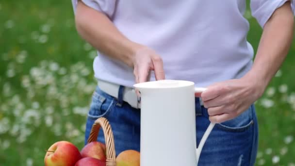 On the background of a chamomile lawn, womens hands pour tea from a white jug into a white cup, a thermos bottle. On the table there is also a basket with red apples.