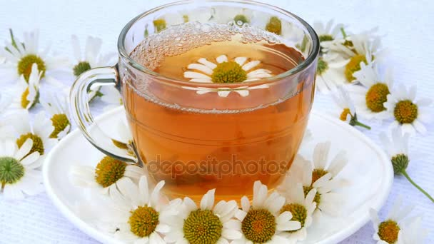 Close-up, transparent, glass cup with chamomile tea, on a white saucer. Everything is decorated with chamomile flowers