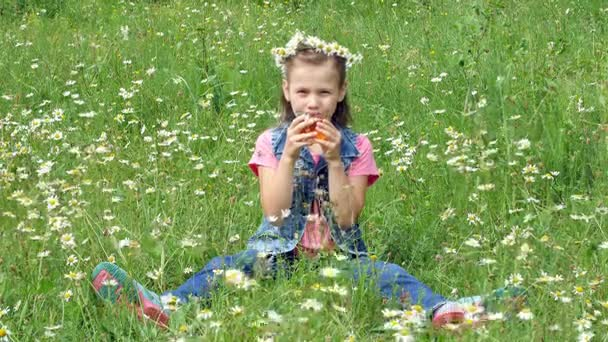 On a chamomile lawn, a sweet girl in a wreath of chamomile, drinking chamomile tea from a glass cup and smiling pretty