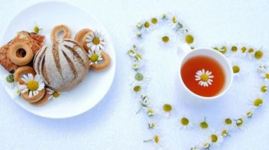 a white plate with pastries, biscuits and cookies, decorated with white daisies. On white saucer there is one white cup with chamomile tea. Around It, there is a heart of chamomiles