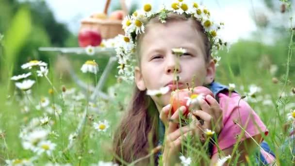 Uprostřed heřmánkový trávník, v trávě leží hezká dívka sedmi let, v věnec sedmikrásky a vesele se apetite, trýznivý, jíst červené jablko