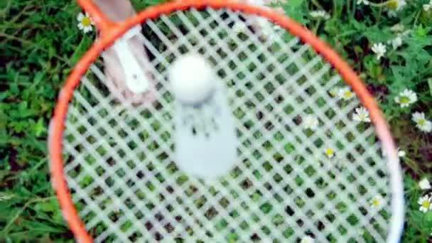Detail, pohled shora. Dítě, chlapec, drží badmintonový míček na badminton raketa