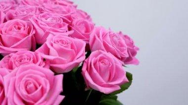 Közelkép, virág, csokor, forgatás, fehér alapon, rózsaszín rózsa áll virág kompozíció. Isteni szépség. Virágbolt