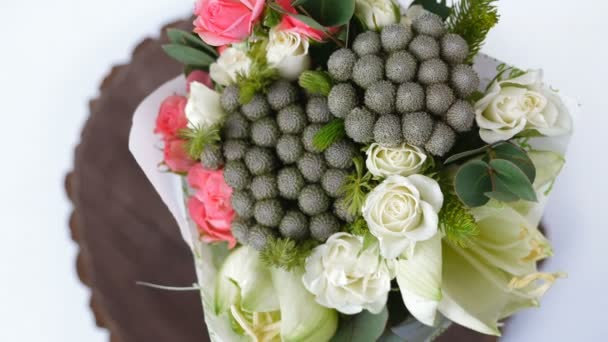 Top view, close-up of a bouquet of flowers, rotation , consists of eucalyptus, cineraria, Rose cream grace, Rose barbados, Eustoma, solidago, Santini , feverweed, Brunia green.