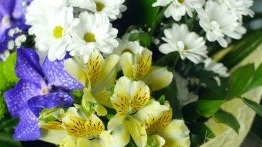Közelkép, felülnézeti, virág csokor, a sugarak a fény, forgatás, virág kompozíció áll Alstroemeria, krizantém bacardi, orchidea vanda, Santini, gypsophila, Eustoma