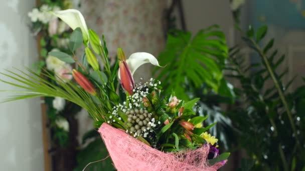Kytice v paprscích světla, rotace, květinové kompozice je tvořena calla lily, Brunia zelená, gypsophila, orchidej vanda, kosatců, aspidistra, Russus