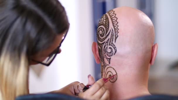 Egy lány, tetováló mester, mehendi művész teszi a fejbőr kopasz kaukázusi Férfi, váll, nyak henna tetoválás rajz. A megoldás a henna kiszárad a bőr