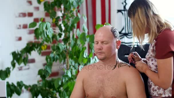 Egy lány, tetováló mester, mehendi művész teszi a hennafestés támaszkodva a fejbőr kopasz kaukázusi Férfi, kék inget, ül a szék. Mehendi, henna tetoválás, jelenleg nagyon népszerű az emberek között, és