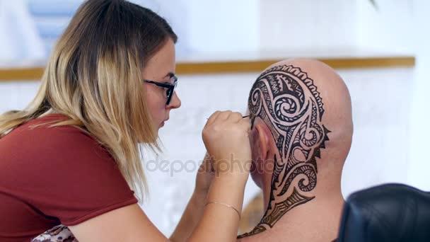 Egy lány, tetováló mester, mehendi művész teszi a fejbőr kopasz kaukázusi Férfi, váll, nyak henna tetoválás rajz. Az eljárás alkalmazása henna egy cső a bőrt