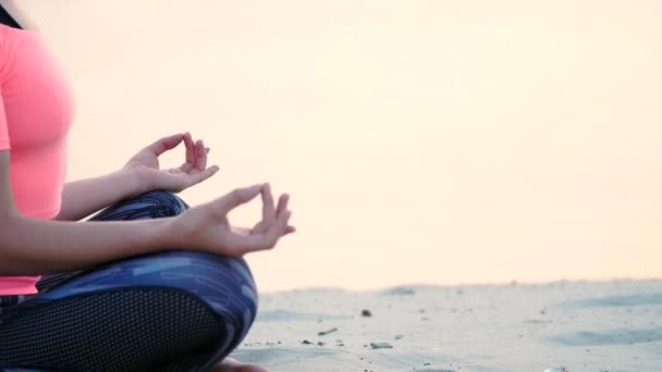 Healthy, young beautiful woman meditating, practicing yoga on the beach, by the sea, at sunrise, Relaxes muscles, mind, acquires the harmony of soul and body. close up