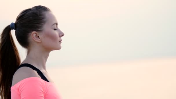 Zdravá, Mladá krásná žena medituje, cvičí jógu na pláži, u moře, na východ, Relaxes svaly, mysl, získává harmonie duše a těla. Detailní záběr