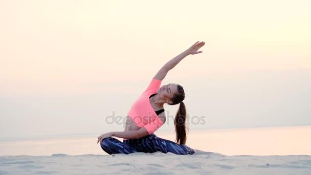 Žena sedí v relaxační jóga pozice na pláži u moře. při východu slunce. Uvolňuje svaly, mysl, získává harmonie duše a těla