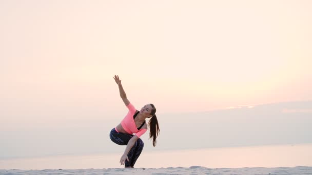 Healthy, young beautiful woman meditating, practicing yoga on the sea beach, at sunrise, Makes exercises for balance and coordination, deep muscle tone.