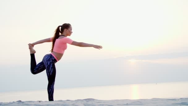 Healthy, young beautiful woman meditating, practicing yoga on the sea  beach, at sunrise, Makes exercises for balance and coordination, deep  muscle tone  close up