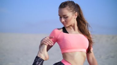 Healthy, young beautiful woman stretching, practicing yoga on the beach, at sunrise, Makes exercises for balance and coordination, deep muscle tone. relaxation of muscles, mind