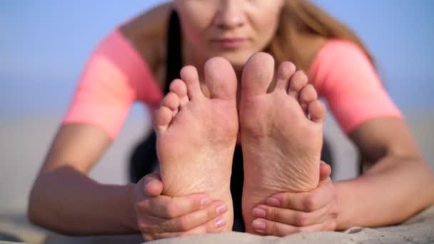 Krásná blondýnka dělá protahovací cvičení na pláži. Detail nohy