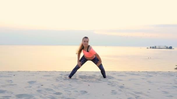 Zdravá, Mladá krásná žena, meditaci, strečink, cvičení jógy na pláži moře za úsvitu, dělá cvičení pro rovnováhu a koordinaci, hluboký svalový tonus