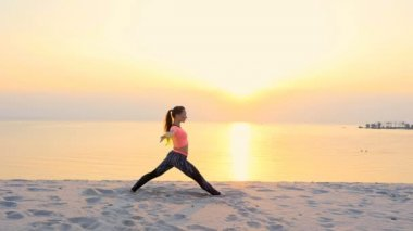Healthy, young beautiful woman meditating, stretching, practicing yoga on the sea beach, at sunrise, Makes exercises for balance and coordination, deep muscle tone