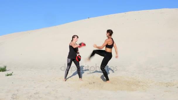 Zwei sportliche, junge Frauen in schwarz Fitness-Anzüge in einem Paar engagieren trainieren Tritte, an einem einsamen Strand, vor blauem Himmel, im Sommer unter einer heißen Sonne