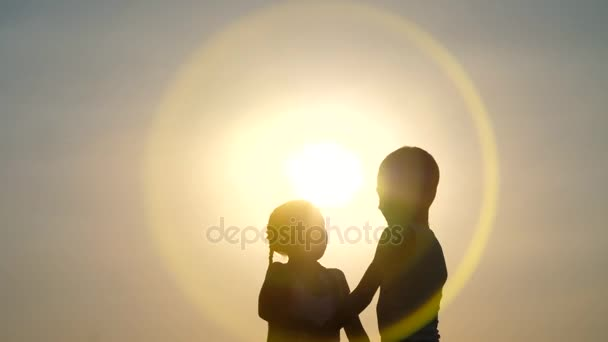 Siluety, postavy dětí, chlapec a dívka skákání, zábava, tanec, objímání na pozadí slunce, při západu slunce v létě. Šťastná rodina. Zpomalený pohyb