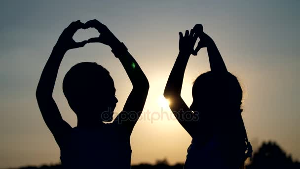 Silhouettes, figures of children, boy and girl show the hearts with the fingers, hands, against the background of the sun, at sunset in summer. Happy family. Slow motion