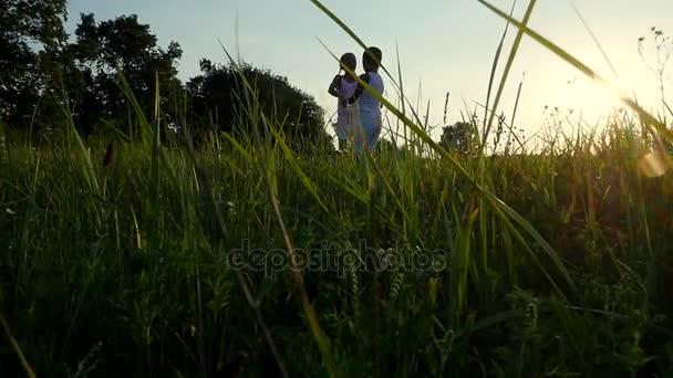 Sagome, figure di bambini, ragazzo e ragazza salto, divertirsi, ballare sullo sfondo del sole, al tramonto in estate. Famiglia felice. Slow motion