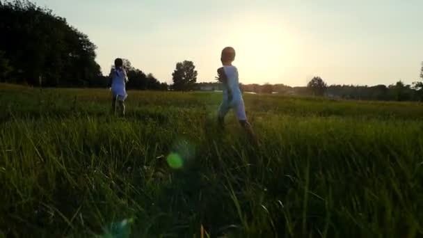 Siluety, postavy dětí, chlapec a dívka jsou spuštěny, baví, na pozadí slunce, při západu slunce v létě. Šťastná rodina. Zpomalený pohyb