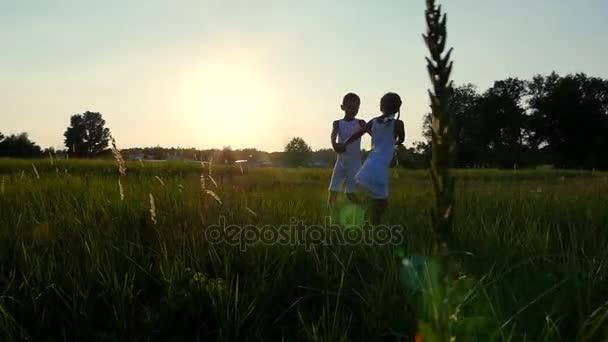 Sziluettek, számok, a gyermekek, a fiú és a lány jumping, szórakozás, tánc, a háttérben az a nap, a naplemente a nyári időszakban. Boldog család. Lassú mozgás