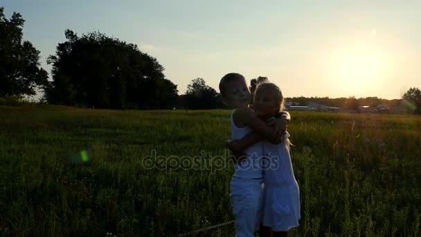 Siluety, postavy dětí, chlapec a dívka objímá na pozadí slunce, při západu slunce v létě. Šťastná rodina. Zpomalený pohyb