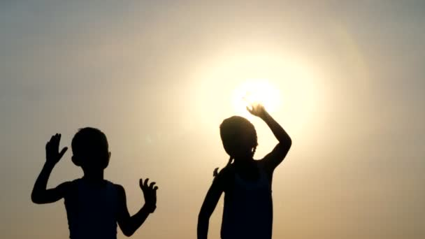 Sagome, figure di bambini, ragazzo e ragazza salto, divertirsi, ballare, che abbracciano contro lo sfondo del sole, al tramonto in estate. Famiglia felice. Slow motion