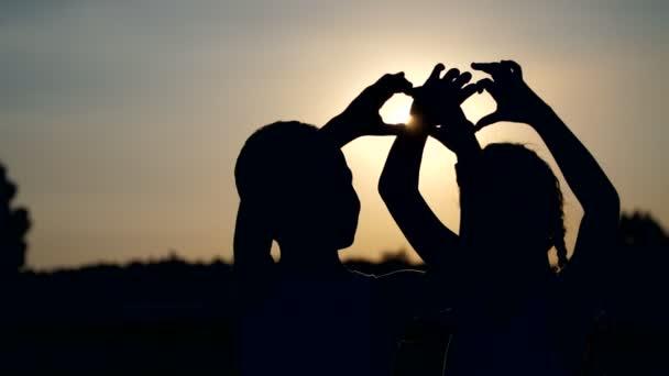 Sagome, figure di bambini, ragazzo e ragazza Visualizza i cuori con le dita, mani, sullo sfondo del sole, al tramonto in estate. Famiglia felice. Slow motion