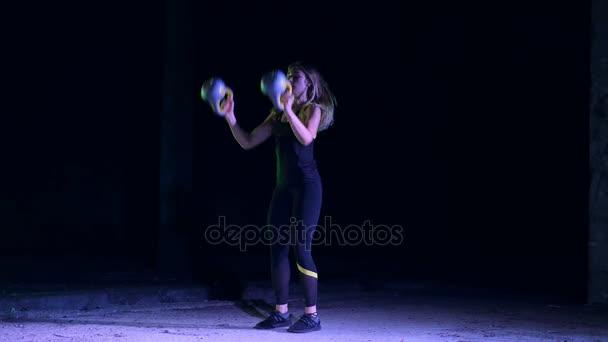 athletische, schöne, junge Frau, die verschiedene Kraftübungen mit Gewichten macht. Nachts, im Licht der bunten Scheinwerfer, im leichten Rauch, Nebel, in einem alten verlassenen Hangar,